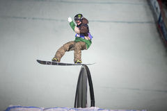 Mann auf Snowboard schiebt auf die Schiene Stockfotografie