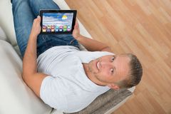 Mann auf Sofa With Laptop Showing Icons stockfoto