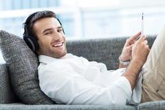 Mann auf Sofa mit digitaler Tablette Stockfoto
