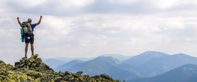 Mann auf Spitze des Berges Emotionale Szene Junger Mann mit backpac lizenzfreie stockbilder