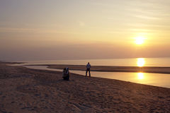 Mann auf Strand am Sonnenuntergang Stockfotos