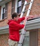 Mann auf Strichleiter auf einem Dach Lizenzfreies Stockbild