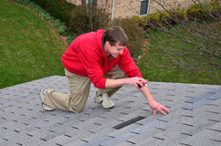 Mann auf Strichleiter auf einem Dach Stockfotos