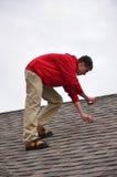 Mann auf Strichleiter auf einem Dach Stockfotografie