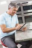 Mann auf Tablette-Computer in Küche-trinkendem Kaffee Stockfotografie