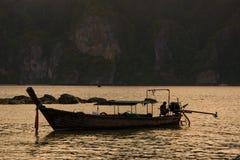 Mann auf Taxiboot des langen Schwanzes auf Sonnenuntergang lizenzfreie stockfotografie