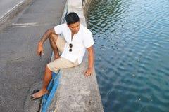 Mann auf Uferdamm im Urlaub stockfotografie