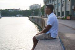 Mann auf Uferdamm im Urlaub lizenzfreies stockbild