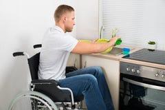 Mann auf waschenden Tellern des Rollstuhls lizenzfreie stockfotografie