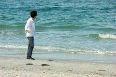 Mann auf werfenden Felsen des Strandes in Ozean Stockfotos