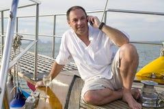 Mann auf Yacht mit Handy und Wein Lizenzfreie Stockbilder