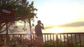 Mann-aufpassender Sonnenaufgang beim Trinken des Kaffees stock video footage