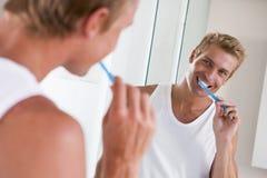 Mann in auftragenden Zähnen des Badezimmers Lizenzfreie Stockfotos