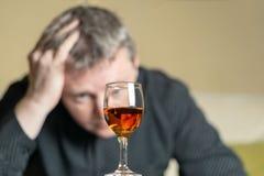 Mann aus Fokusblicken auf ein Glas Weinbrand heraus lizenzfreie stockfotografie