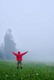 Mann ausgestreckte Hände beim Genießen des nebeligen Morgens Stockfotografie
