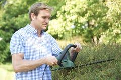 Mann-Ausschnitt-Garten-Hecke mit elektrischem Trimmer Lizenzfreies Stockbild