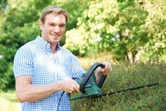 Mann-Ausschnitt-Garten-Hecke mit elektrischem Trimmer stockfotos