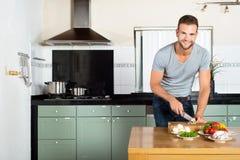 Mann-Ausschnitt-Gemüse an der Küchenarbeitsplatte stockfotos
