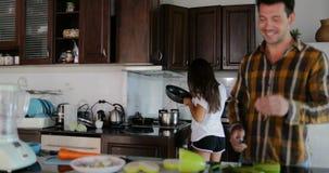 Mann-Ausschnitt-Gemüse, Frau mit dem Braten von Pan Preparing Healthy Dinner Couple in der Küche zusammen sprechen kochend glückl stock video