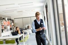 Mann avec le téléphone portable dans le bureau Image libre de droits