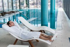 Mann in Bademantelentspannendem nahem Innenswimmingpool im Luxusbadekurort lizenzfreie stockbilder