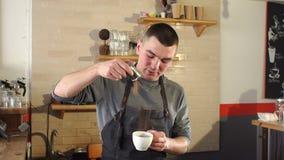 Mann barista goss in einen Tasse Kaffee-Zimt in einer modernen Kaffeestube stock video footage
