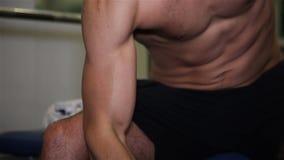 Mann baut die Muskeln auf, die einen Dummkopf in der Turnhalle anheben stock video footage