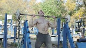 Mann baut seine Muskeln auf dem Simulator auf stock video