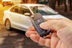 Mann bedrängt Knopf auf Zündschlüssel mit Wegfahrsperre auf dem Hintergrund des Autos Stockbilder