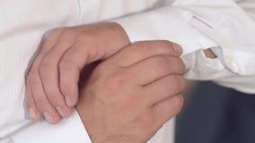 Mann befestigt Knöpfe auf Ärmel des weißen Hemdes, Mann setzt an ein weißes Hemd stock video