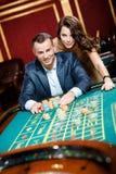 Mann begleitet von der Frau am Roulettetisch Stockbild