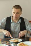 Mann bei Tisch mit Pizza Stockfotos