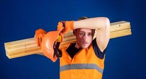 Mann beim Abwischen des Sturzhelms und der Schutzhandschuhe geschwitzt von der Stirn, blauer Hintergrund Müdes Arbeiterkonzept ti Lizenzfreie Stockfotos