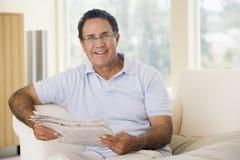 Mann beim Wohnzimmerlesezeitungslächeln Lizenzfreie Stockfotos