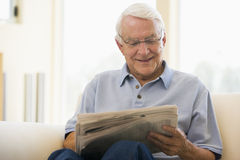 Mann beim Wohnzimmerlesezeitungslächeln Lizenzfreie Stockbilder