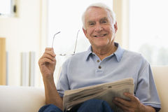 Mann beim Wohnzimmerlesezeitungslächeln Stockfoto