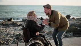 Mann belebt seine geliebte Frau, die im Rollstuhl im Seestrand sitzt stock video footage