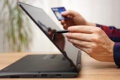 Mann benutzt Debet oder Kreditkarte, um online auf tragbarem touc zu zahlen lizenzfreies stockfoto
