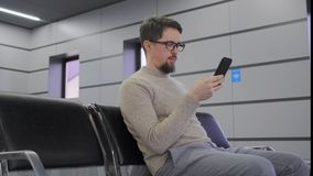 Mann benutzt den Smartphone, der im Flughafen sitzt stock video
