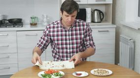 Mann bereitet Bestandteile für shawarma auf dem Küchentisch zu Hause kochen vor Pittabrot, Gemüse und Frühlingszwiebel mit stock video footage
