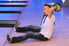 Mann bereitet vor sich, in Bowlingspielklumpen zu werfen Stockbild