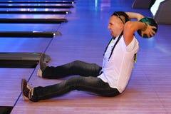 Mann bereitet vor sich, in Bowlingspielklumpen zu werfen Stockfotografie