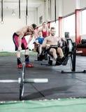 Mann-bereitstehende Freunde, die auf Rudermaschine trainieren stockfotografie