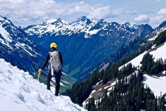 Mann-Bergsteiger, der auf die Gebirgsoberseite steht und Ansicht genießt Stockfotos