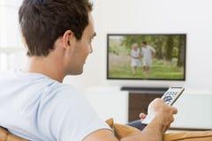 Mann in überwachendem Fernsehen des Wohnzimmers Stockfotografie