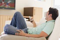 Mann in überwachendem Fernsehen des Wohnzimmers Lizenzfreies Stockfoto