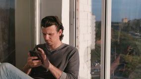 Mann betrachtet den Handy und schlägt das Band in den sozialen Netzwerken leicht, die auf dem Balkon bei Sonnenuntergang sitzen stock video footage