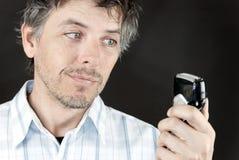 Mann betrachtet elektrisches Raxor Stockbild