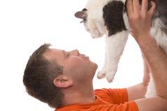 Mann betrachtet oben der Katze, die auf Weiß getrennt wird Lizenzfreie Stockfotos