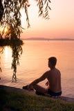 Mann bewundern den Sonnenuntergang auf dem See Lizenzfreies Stockfoto
